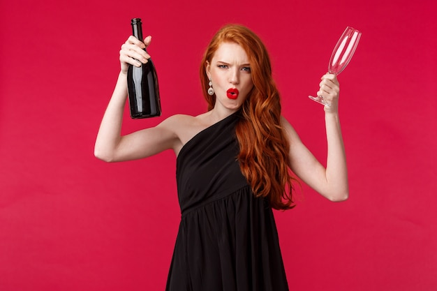 Concept de célébration, de vacances et de femmes. impertinente et insouciante, excitée jeune femme rousse s'amusant à la fête, soulevant une bouteille de champagne et un verre, invitant tout le monde à boire, à l'audace