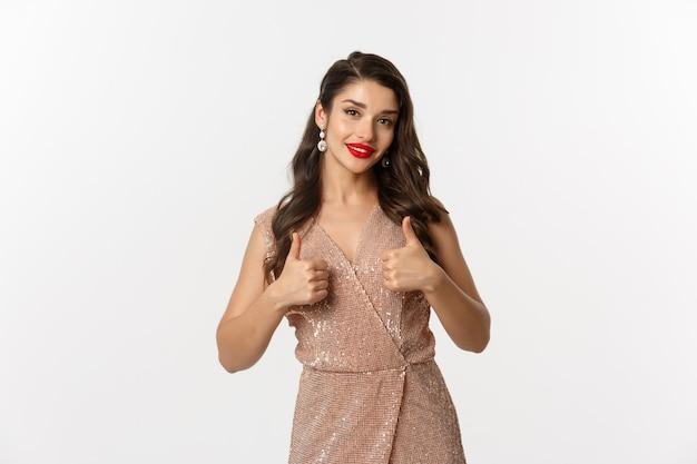Concept de célébration, de vacances et de fête. beau modèle féminin aux lèvres rouges, vêtue d'une robe glamour et montrant le pouce en l'air en signe d'approbation, comme et d'accord, loue un bon choix.