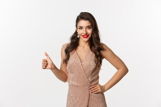 Concept de célébration, de vacances et de fête. femme séduisante et confiante aux lèvres rouges, vêtue d'une robe de soirée de luxe et montrant le pouce vers le haut, approuver et aimer, fond blanc