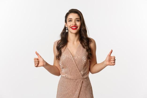 Concept de célébration, de vacances et de fête. modèle féminin attrayant en robe luxueuse, montrant les pouces vers le haut et souriant satisfait, approuver et aimer, debout sur fond blanc