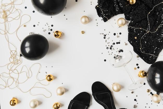 Concept de célébration de vacances de noël. or, confettis noirs, verre à champagne, robe féminine, ballons, highheels, boules sur fond blanc