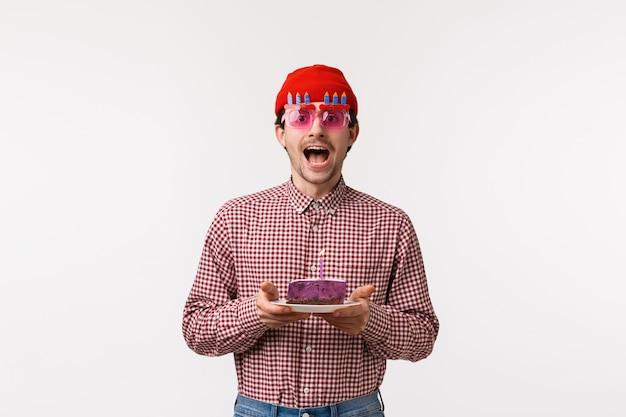 Concept de célébration, de vacances et de style de vie. excité heureux beau barbu adulte mec célébrant l'anniversaire avec des amis dans des verres drôles, tenant le gâteau du jour b avec une bougie allumée, faire un souhait