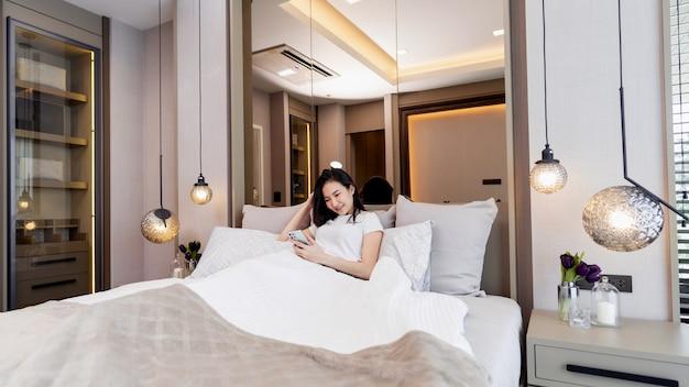 Concept de chambre à coucher une fille avec une sensation de somnolence allongée sur plusieurs grands et confortables oreillers regardant sur l'écran du mobile pour la mise à jour de l'actualité.