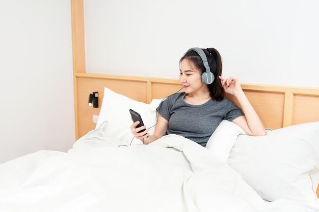 Concept de chambre sur le lit confortable une fille écoutant ses chansons préférées en portant un casque le matin.