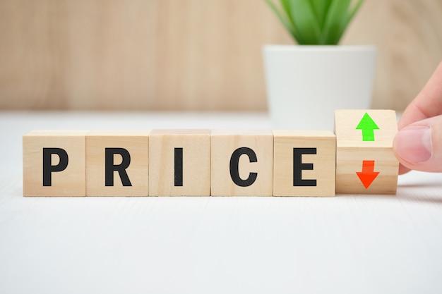 Concept de changement de prix tombant et augmentant de manière abstraite sur des blocs de bois.