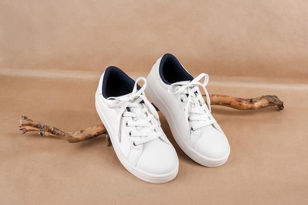 Concept de chaussures végétaliennes éthiques. paire de baskets blanches sur l'accroc en bois, fond de papier kraft beige neutre.