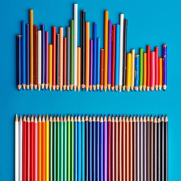 Concept de chef, équipe de nouveaux crayons devant une équipe de crayons usagés, nouvelle idée unique dans une vieille entreprise cassée, gros plan sur papier bleu