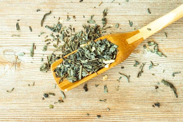 Concept chinois, feuilles de thé vert japonais séchées au bambou scoop close up sur la vue de dessus en bois naturel. espace de copie de texte