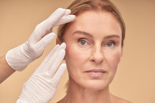 Concept de chirurgie plastique mains d'esthéticienne dans des gants blancs vérifiant la peau du visage féminin avant l'examen médical