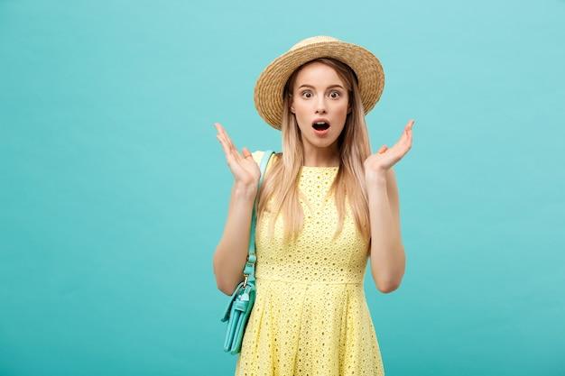 Concept de choc ou de bonne nouvelle : jeune fille blonde élancée aux cheveux longs dans un chapeau se dresse sur un fond bleu isolé. elle ouvrit la bouche de surprise.