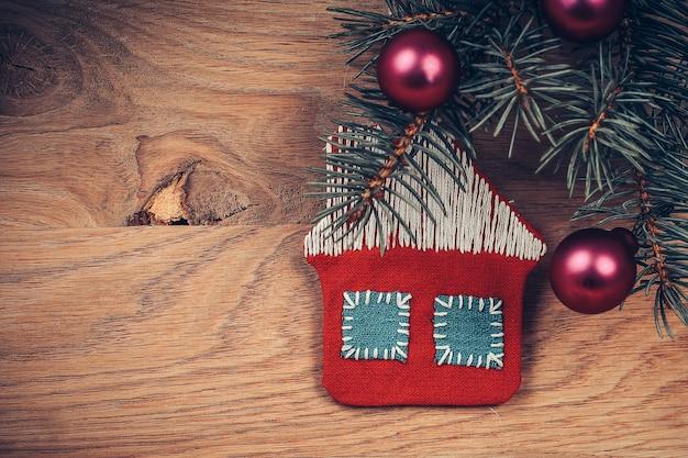 Concept de christmas.knitted house et branche de pin sur fond en bois. place pour le texte