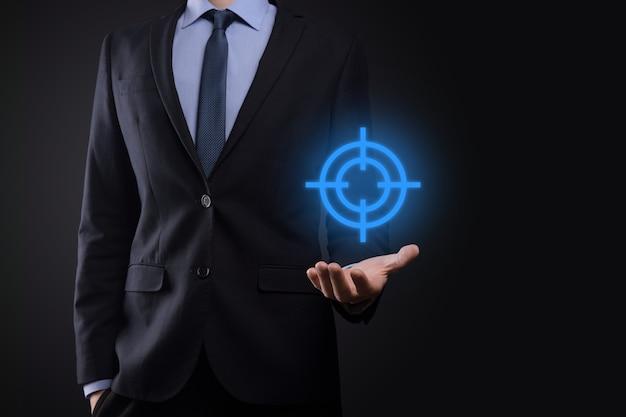 Concept de ciblage avec main d'homme d'affaires tenant croquis de cible de fléchettes symbole sur tableau noir. objectif objectif et concept de but d'investissement.