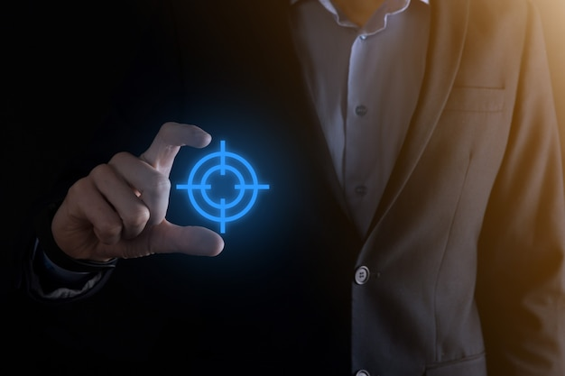 Concept de ciblage avec main d'homme d'affaires tenant croquis de cible icône cible sur tableau noir. objectif objectif et concept de but d'investissement.