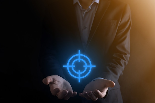 Concept de ciblage avec main d'homme d'affaires tenant le croquis de cible icône cible sur tableau noir. objectif objectif et concept de but d'investissement.