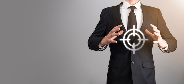 Concept de ciblage avec la main d'homme d'affaires tenant l'esquisse de cible de fléchettes sur le tableau. objectif objectif et concept d'objectif d'investissement.
