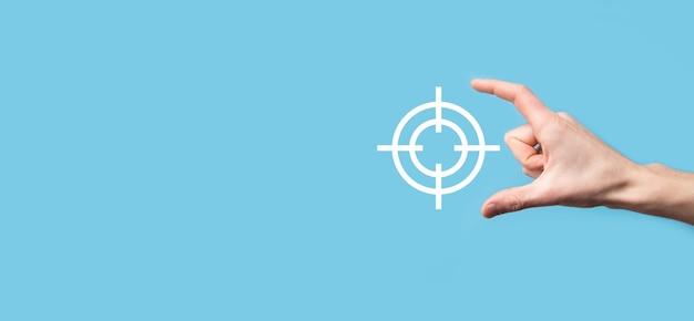 Concept de ciblage avec main tenant croquis de jeu de fléchettes icône cible sur tableau noir