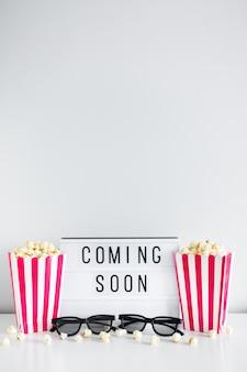 Concept de cinéma - boîtes à rayures avec pop-corn, lunettes 3d, boîte à lumière avec texte