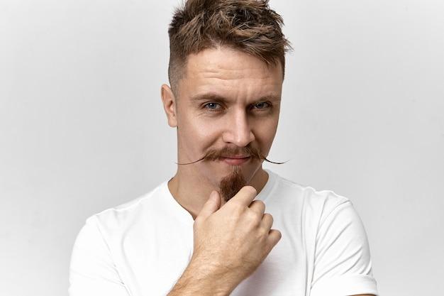 Concept de coiffure, mode et style. photo de l'homme à la mode avec coupe de cheveux élégante, moustache et barbiche regardant la caméra avec un sourire mystérieux, à la recherche de sous ses sourcils épais
