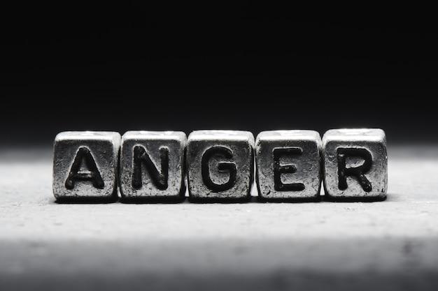 Le concept de colère, technique de gestion des émotions. mot sur des cubes métalliques isolés sur fond noir.