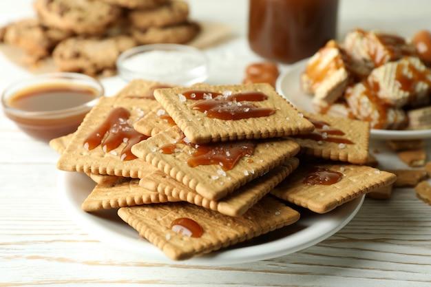 Concept de collation savoureuse avec des cookies au caramel sur une table en bois blanc