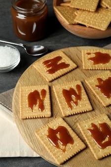 Concept de collation savoureuse avec des cookies au caramel sur une table en bois sombre