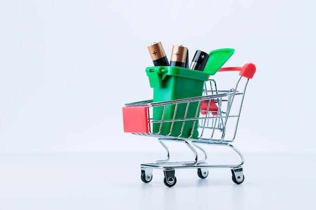 Concept de collecte et de recyclage des piles usagées. corbeille de batterie dans un chariot sur une surface grise.