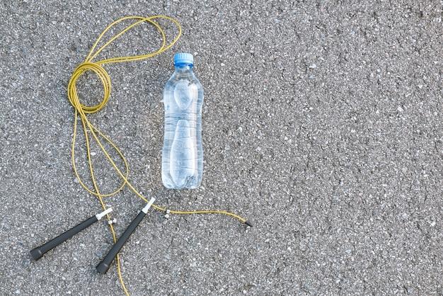 Concept de combustion des graisses. bouteille d'eau près de la corde à sauter