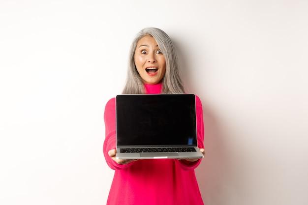 Le concept de commerce électronique a étonné une femme âgée asiatique montrant un écran d'ordinateur portable vierge et semblant heureuse de démontrer...