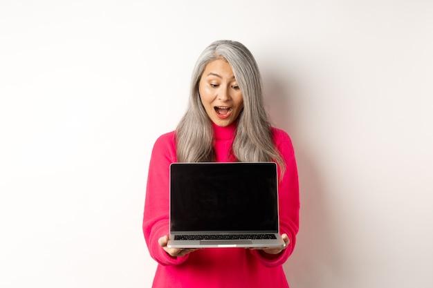 Le concept de commerce électronique a étonné la grand-mère asiatique aux cheveux gris vérifiant la promo en ligne montrant un ordinateur portable ...