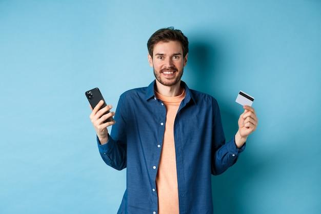 Concept de commerce électronique. excité jeune homme tenant smartphone et carte de crédit en plastique, achats en ligne, debout sur fond bleu.
