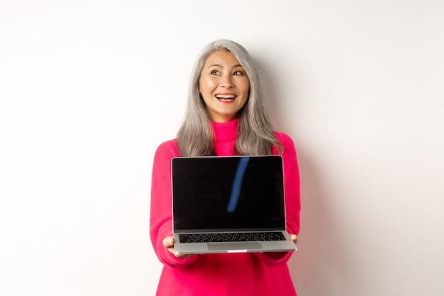 Concept de commerce électronique heureuse belle femme âgée asiatique aux cheveux gris regardant de côté et souriant montrant...