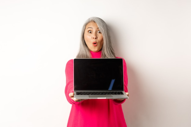 Le concept de commerce électronique a impressionné une femme âgée asiatique montrant un écran d'ordinateur portable vierge et regardant émerveillée par la caméra ...
