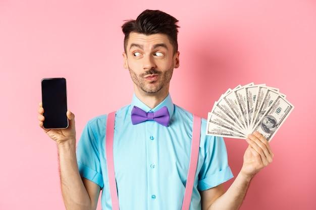 Concept de commerce électronique et de magasinage. drôle de gars regarde curieux à l'écran du smartphone vide, montrant de l'argent, achetant en ligne, debout sur fond rose.