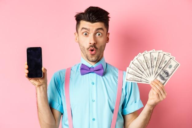 Concept de commerce électronique et de magasinage. homme surpris montrant un écran de smartphone vierge et de l'argent, disant wow avec un visage étonné, vérifiant l'offre en ligne, fond rose.