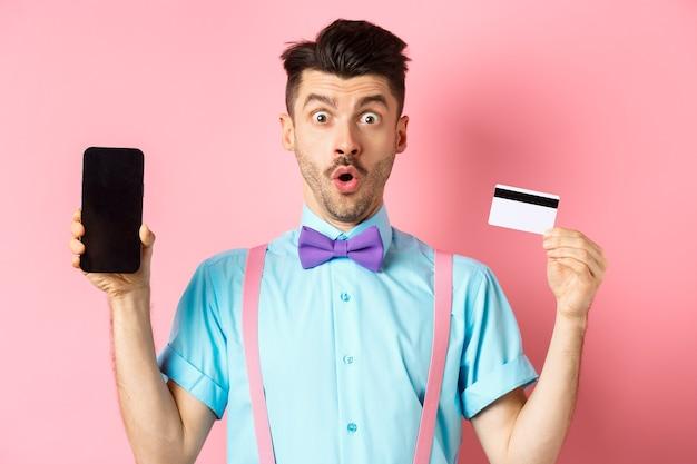 Concept de commerce électronique et de magasinage. surpris homme montrant l'écran du smartphone vierge avec carte de crédit en plastique, debout étonné sur fond rose.