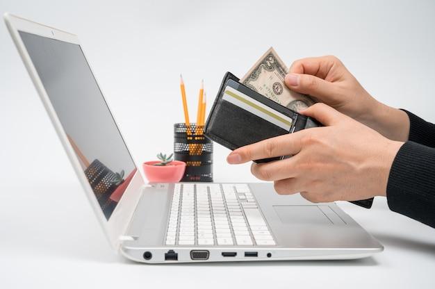 Concept de commerce électronique. la main d'un homme tire de l'argent de son portefeuille devant un écran d'ordinateur portable.