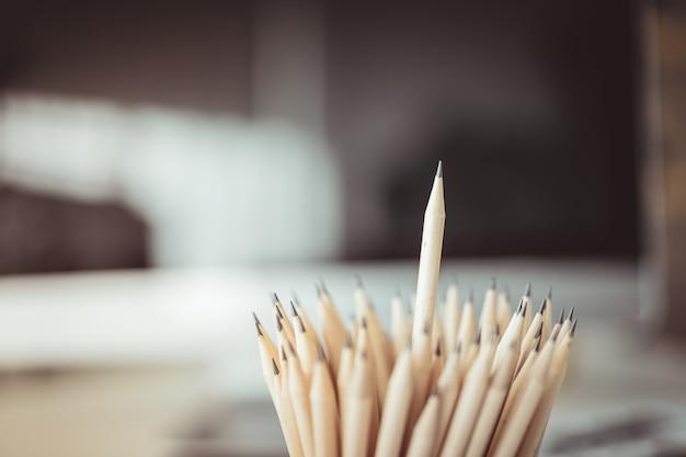 Concept commercial - beaucoup de crayons et le crayon est plus haut que l'autre sur fond flou.