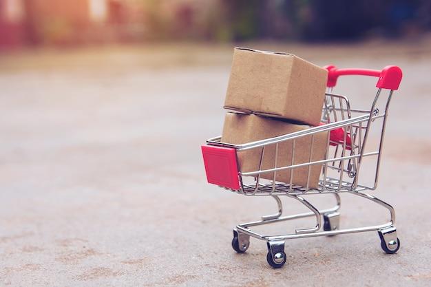 Concept commercial: cartons ou boîtes de papier dans le panier. achats en ligne à domicile