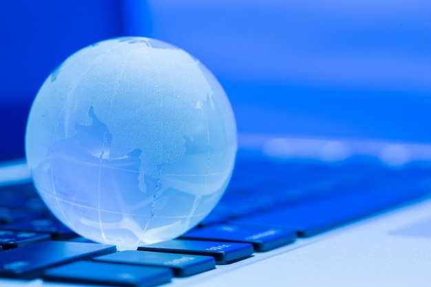 Le concept commercial du monde du verre sur un ordinateur portable