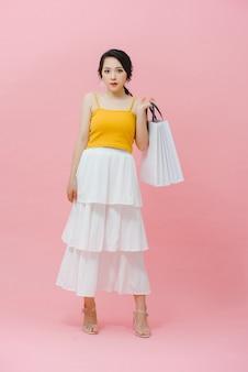 Concept commercial : femme à la mode souriante heureuse portant des vêtements à la mode posant avec des sacs en papier blanc