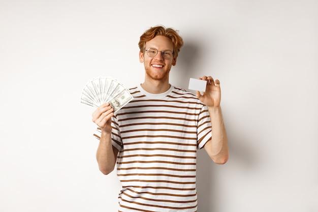 Concept commercial et financier. jeune homme rousse avec barbe et lunettes montrant une carte de crédit en plastique avec de l'argent en dollars, fond blanc.