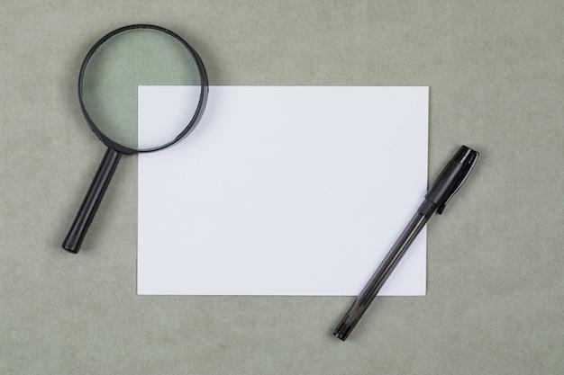 Concept commercial et financier avec loupe, stylo, papier vierge sur fond gris à plat.