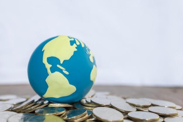 Concept commercial et financier mondial. gros plan d'une mini-balle mondiale sur un tas de pièces de monnaie sur une table en bois et un espace de copie.