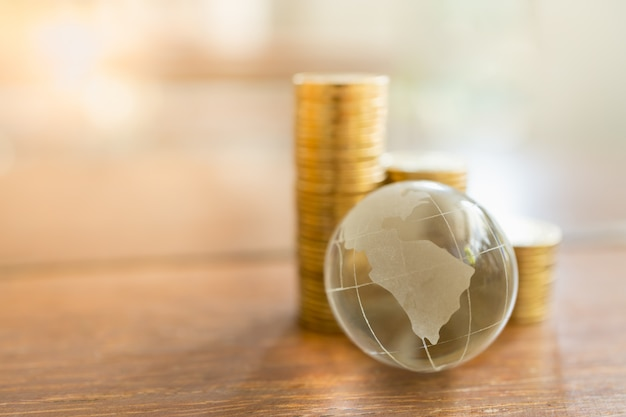 Concept commercial et financier mondial. gros plan de la mini boule de cristal clair avec pile de pièces d'or sur table en bois et espace de copie.