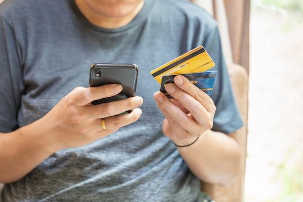 Concept commercial, financier, de paiement et de technologie. homme asiatique tenant deux fausses cartes de crédit de maquette et utilisant un smartphone mobile.