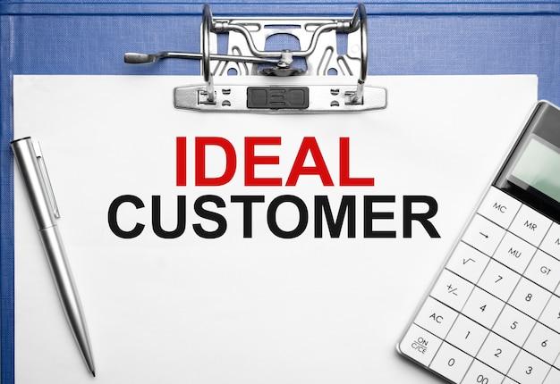 Concept commercial et financier. sur la table se trouvent un cahier, un stylo, une calculatrice et un dossier avec l'inscription ideal customer
