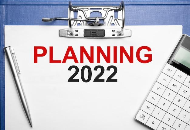 Concept commercial et financier. sur la table se trouvent un cahier, un stylo, une calculatrice et un dossier avec l'inscription planning 2022