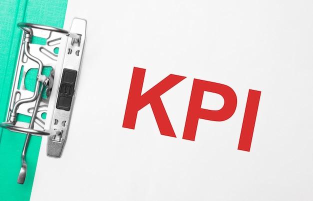 Concept commercial et financier. sur la table se trouvent un cahier, un stylo, des documents et un dossier avec l'inscription kpi