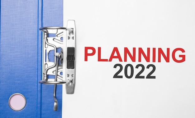 Concept commercial et financier. sur la table se trouvent un cahier, un stylo, des documents et un dossier avec l'inscription planning 2022