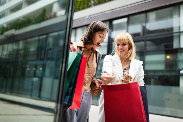 Concept commercial et touristique. belles femmes amies avec des sacs à provisions en ctiy